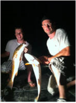 two men holding up larger redfish on the deck of a boat in the dark in st bernard parish marsh
