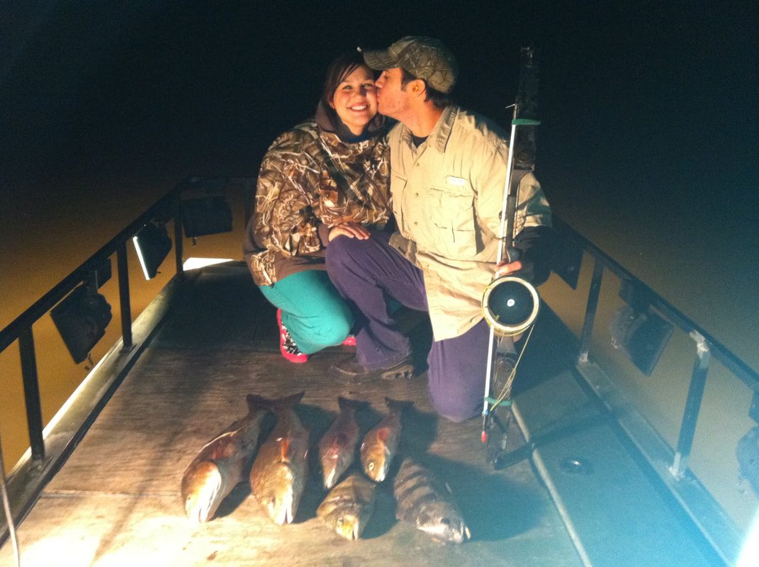 A man kising a woman of the cheek while posing in front of a stringer of bass on the deck of a boat at night in st bernard parish